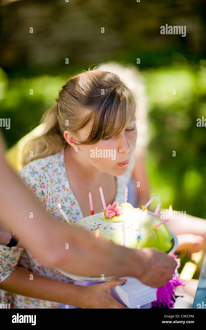 Girl blowing out candles on birthday cake - Stock Image