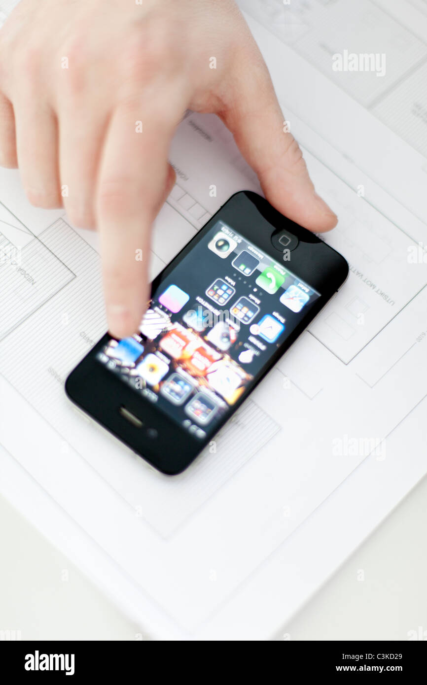 Human finger touching mobile phone on blueprint - Stock Image