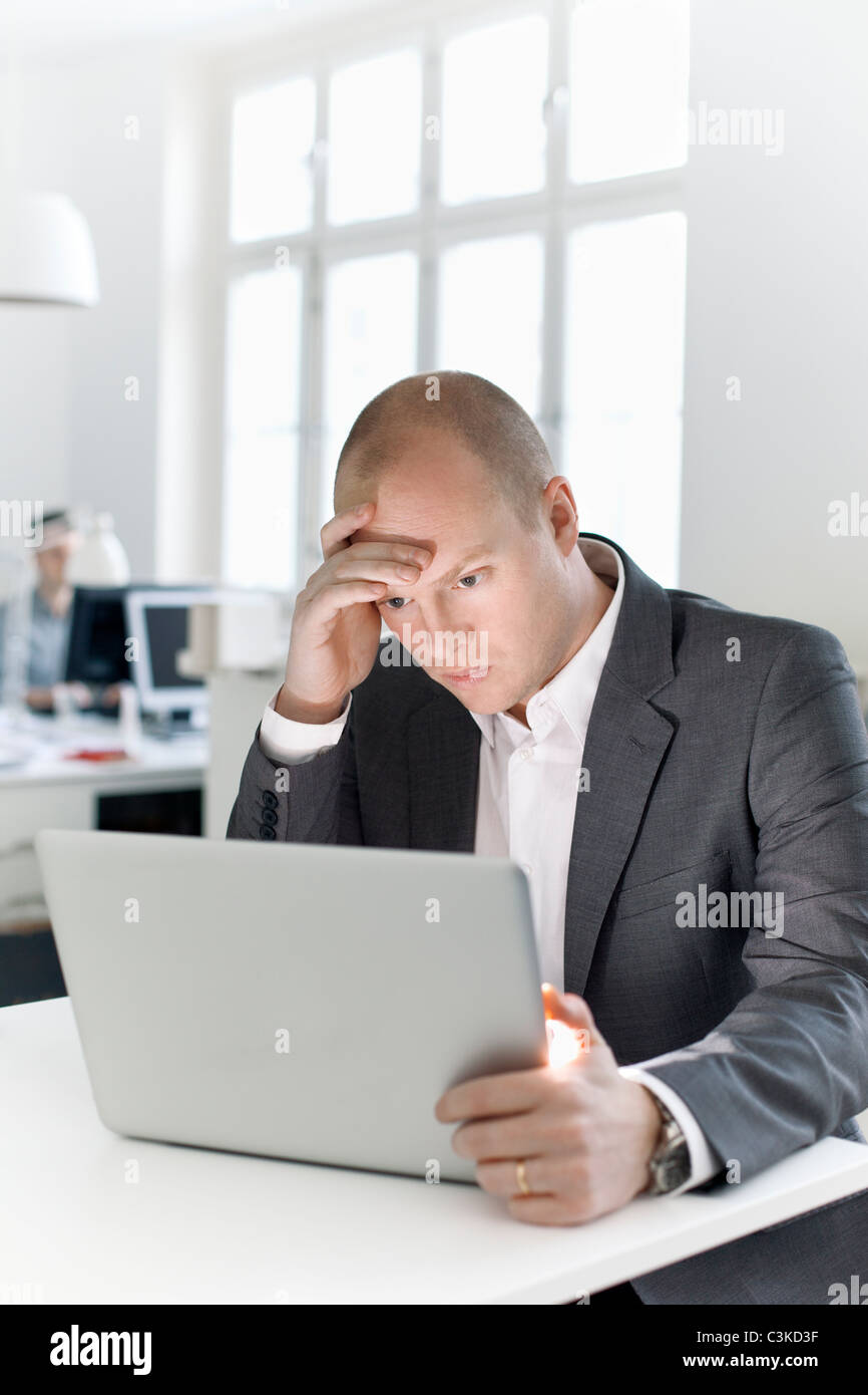 Man sitting in office looking at laptop - Stock Image