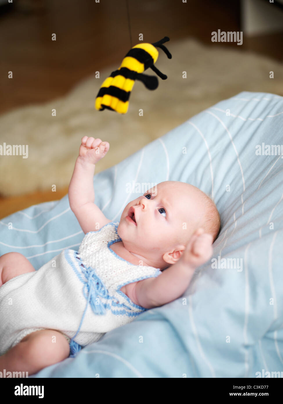 Baby playing with toy wasp - Stock Image