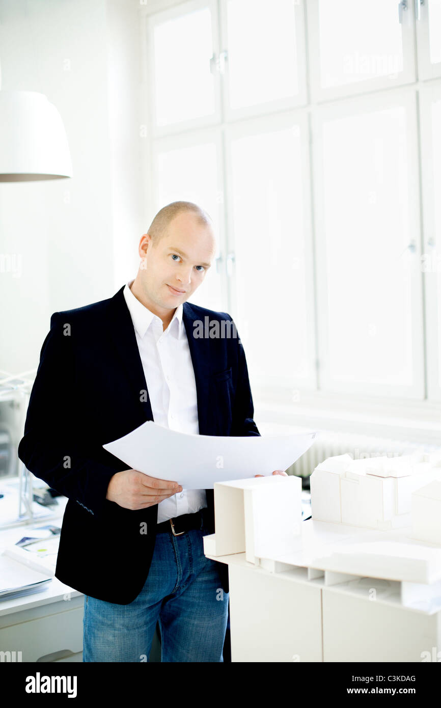 Man standing by model houses in office - Stock Image