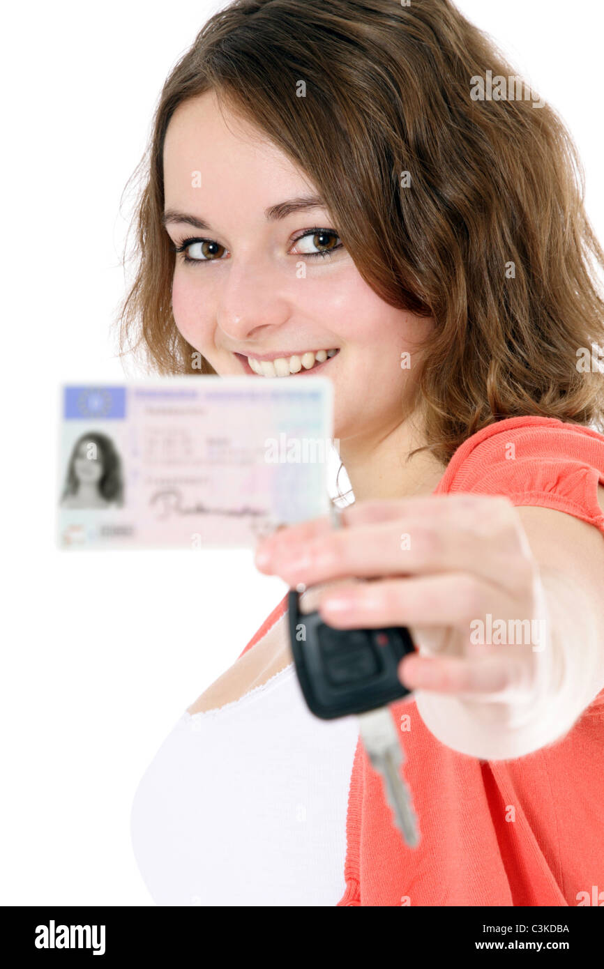 Young woman showing her driver license and car keys. License details blurred out. All on white background. Stock Photo