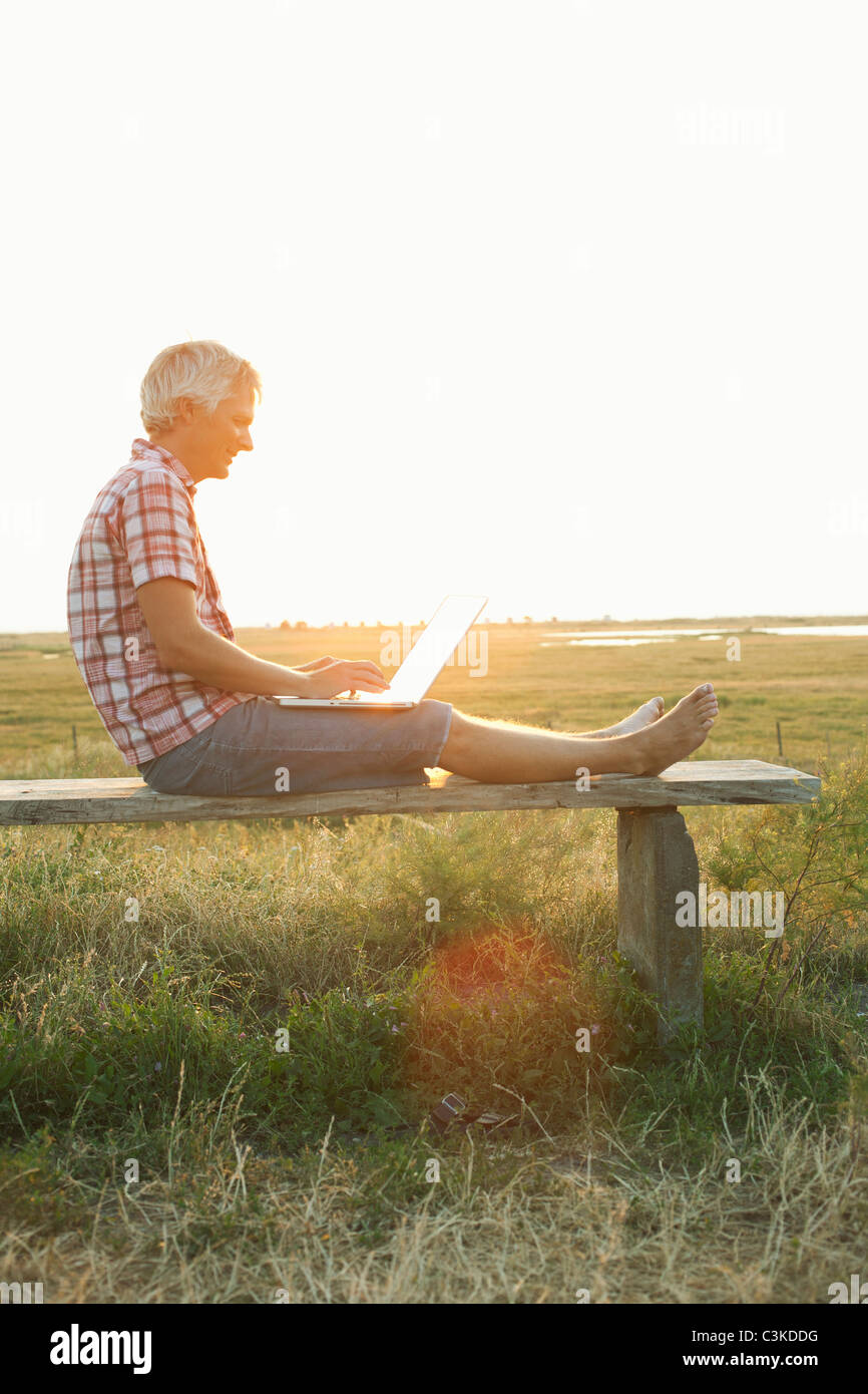 Man sitting on bench using laptop - Stock Image