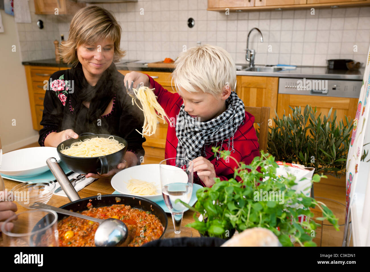 Mother and son eating spaghetti - Stock Image
