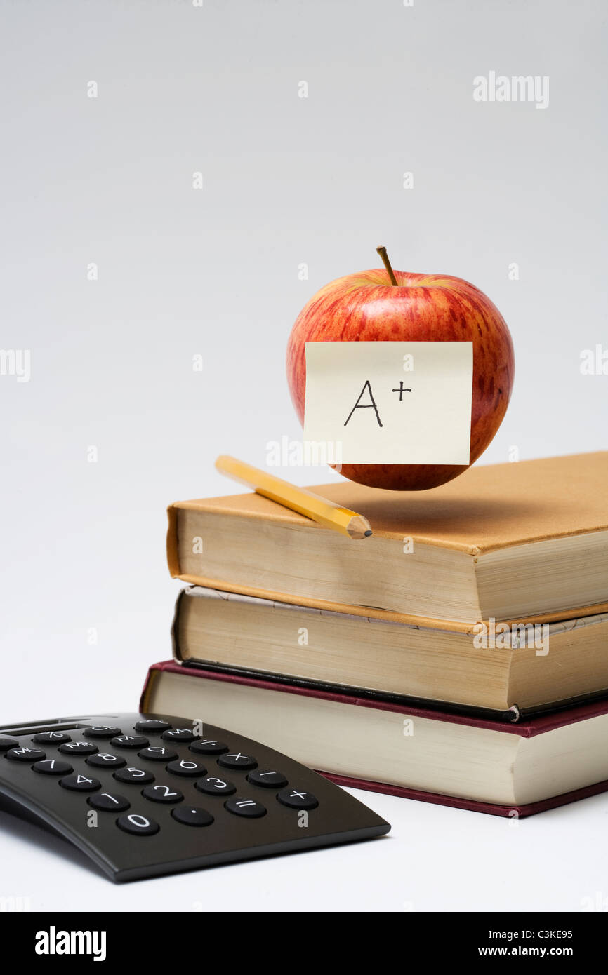An apple on a stack of books, close-up. Stock Photo
