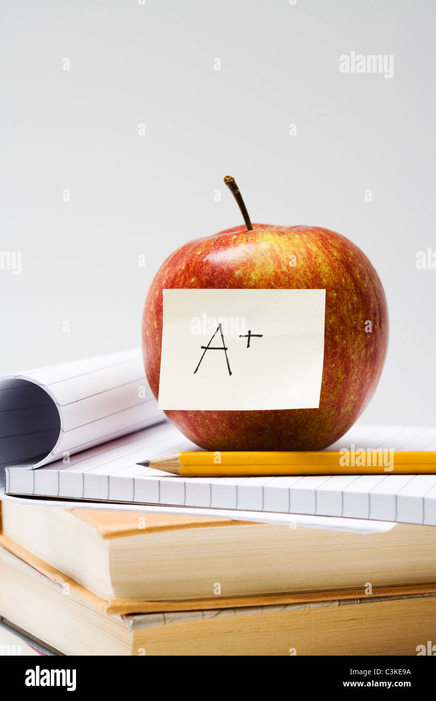 An apple on a note pad, close-up. - Stock Image