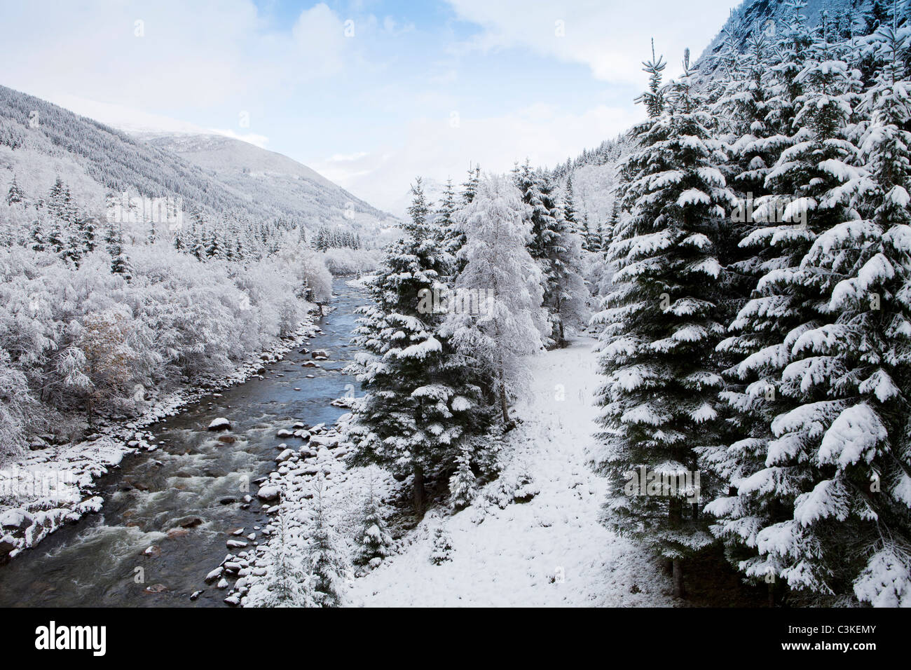 View of stream and snow covered trees, Stordal, Norway. - Stock Image