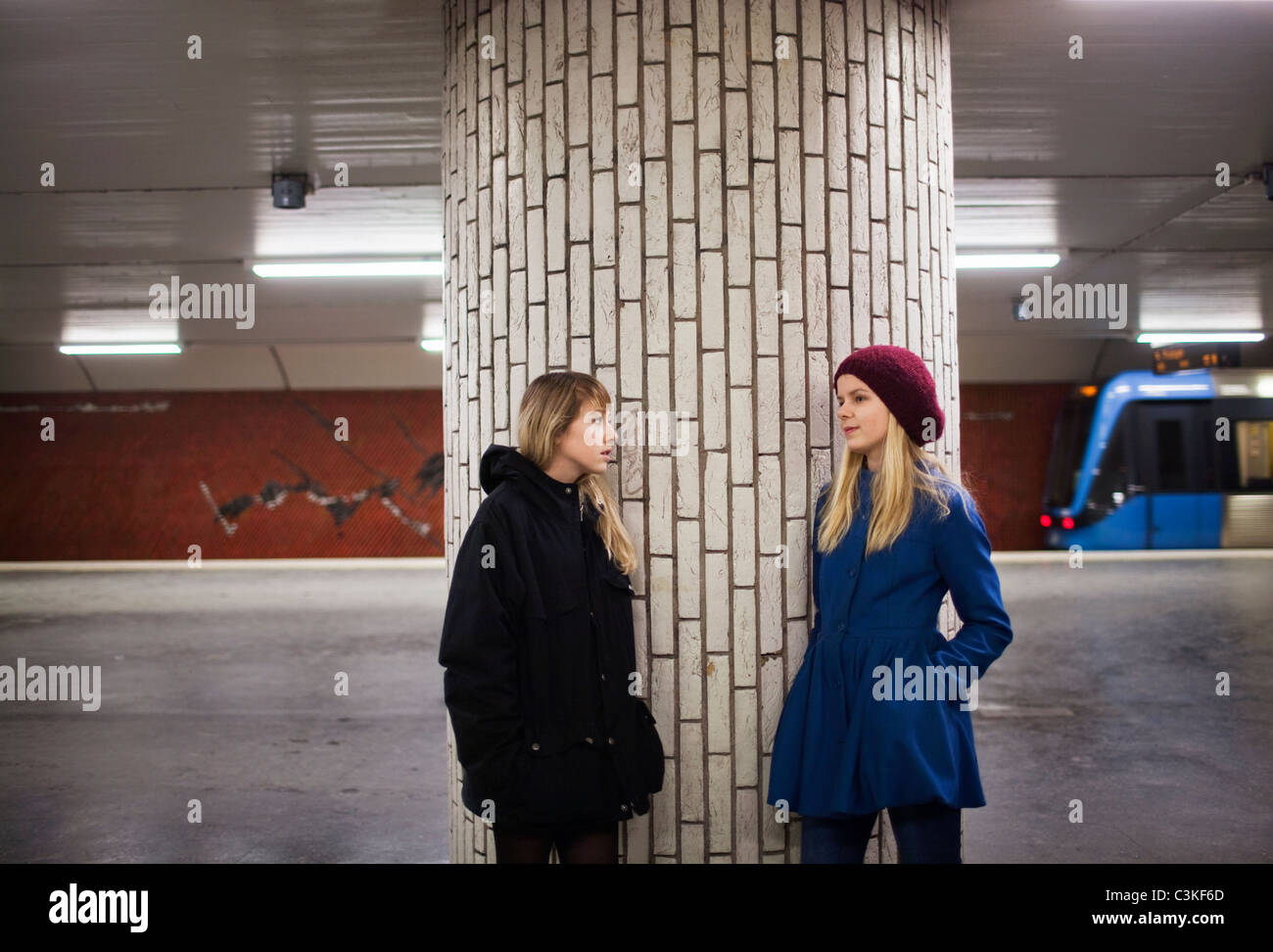 Teenage girls (14-15) talking on railway platform - Stock Image