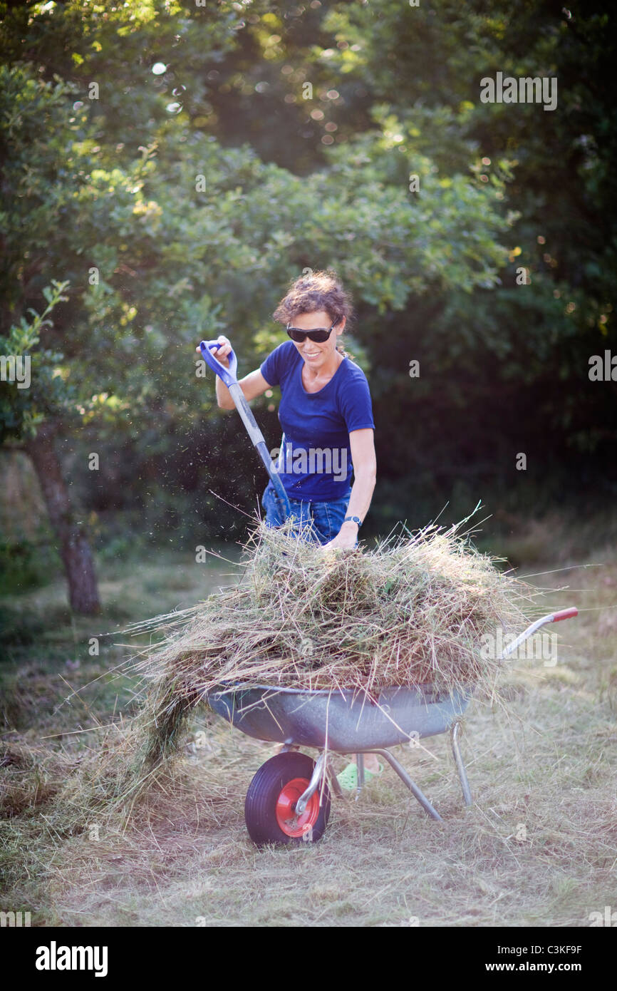 Woman filling wheelbarrow with grass - Stock Image