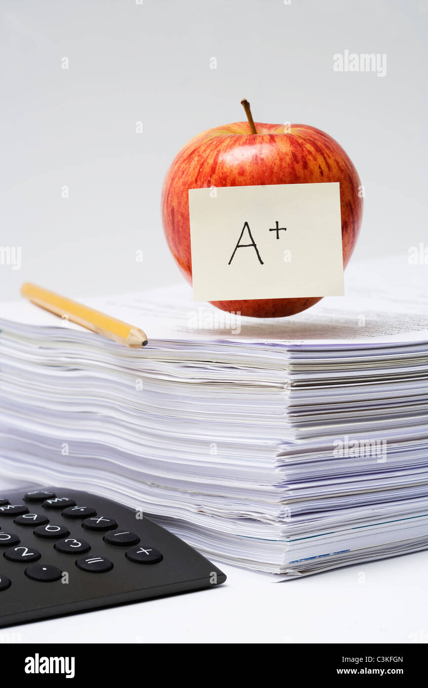 An apple on a stack of paper, close-up. Stock Photo
