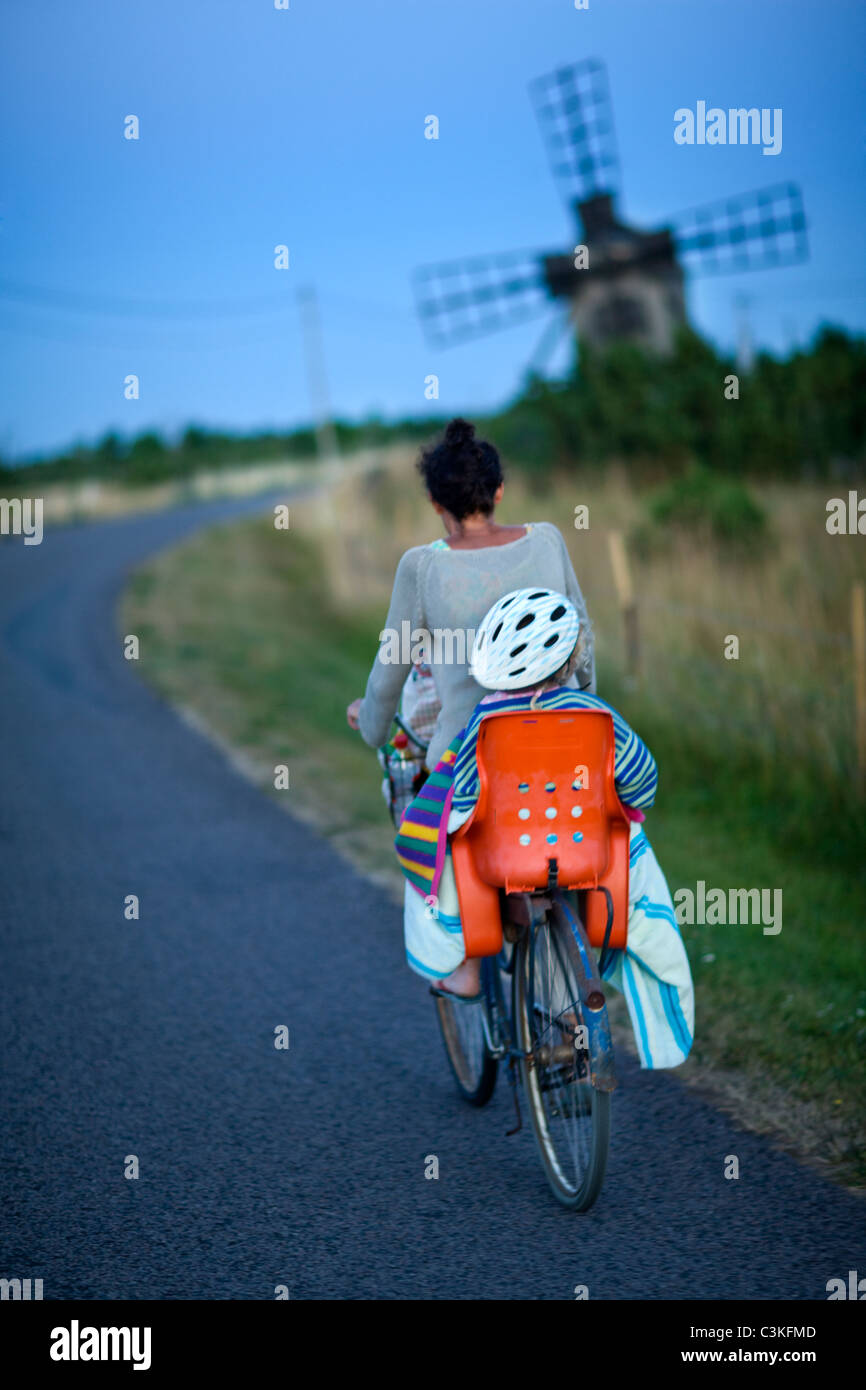 Mother and child riding bicycle, rear view - Stock Image