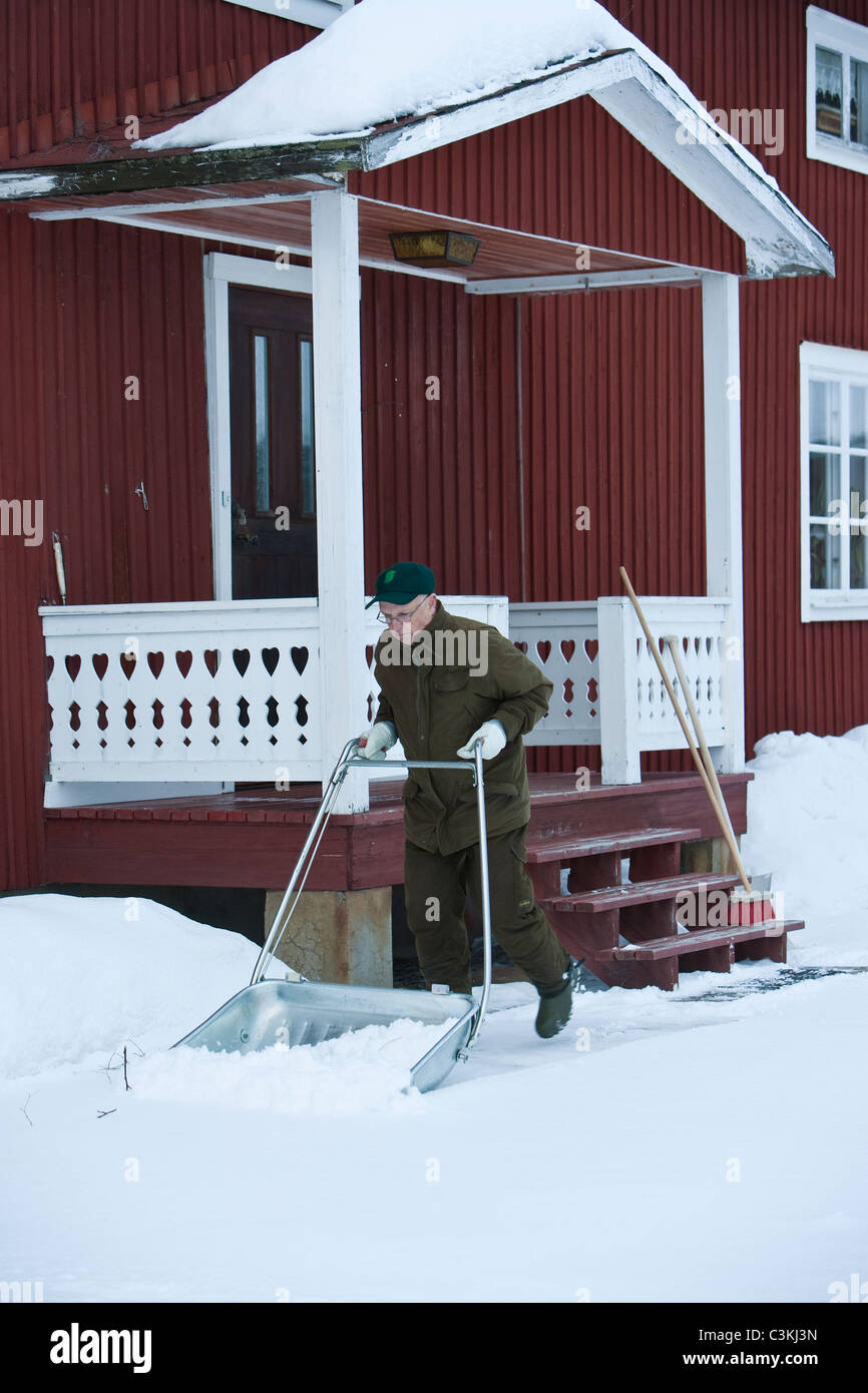 A man clearing away the snow, Sweden. - Stock Image