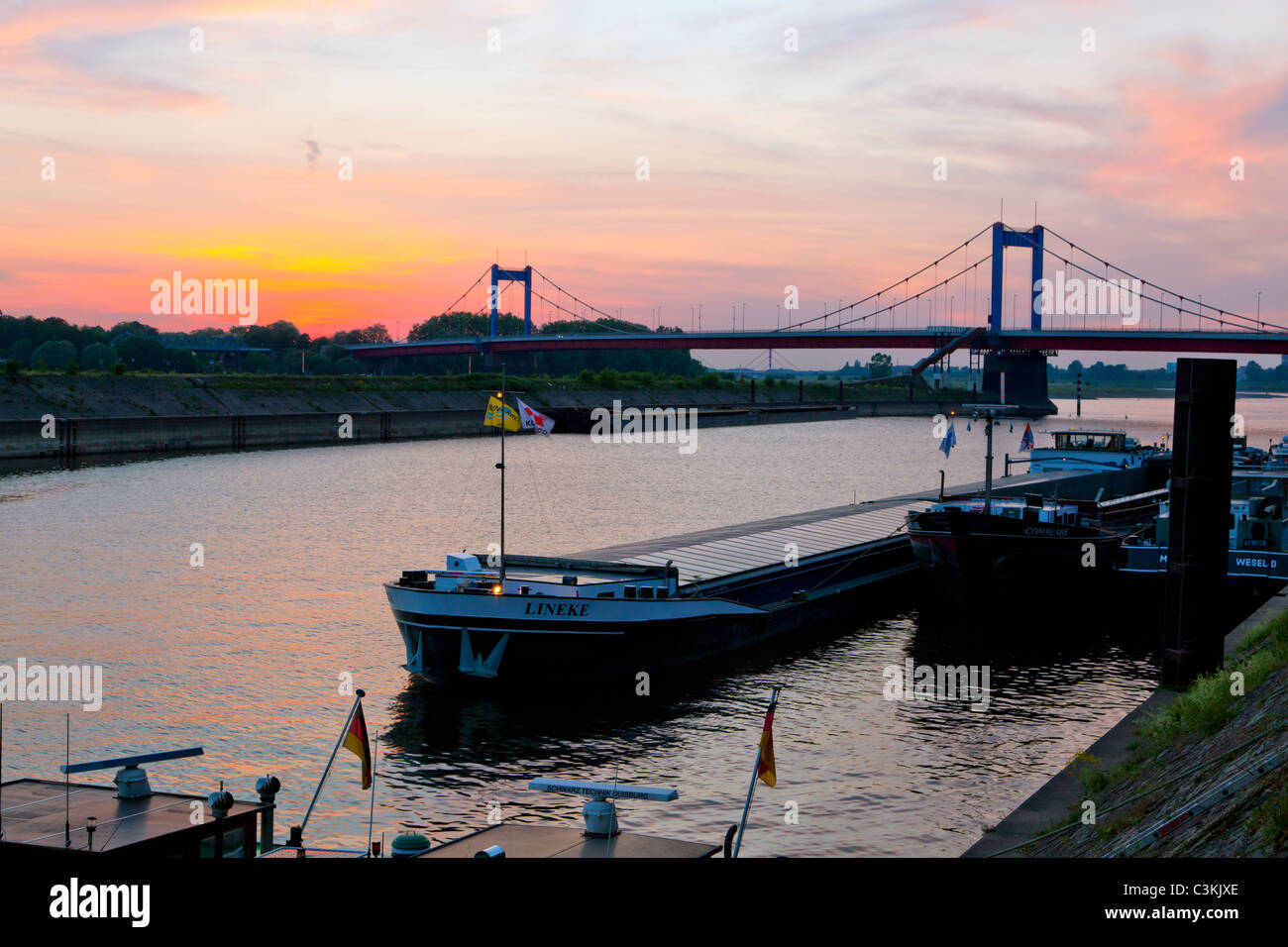 freight ships at the harbor of Duisburg-Ruhrort at sunset - Stock Image