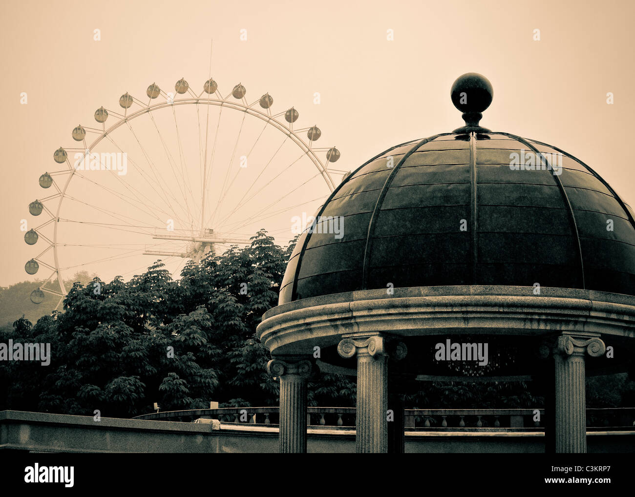 Antiqued effect on a columned pagoda and ferris wheel, off in the distance. - Stock Image