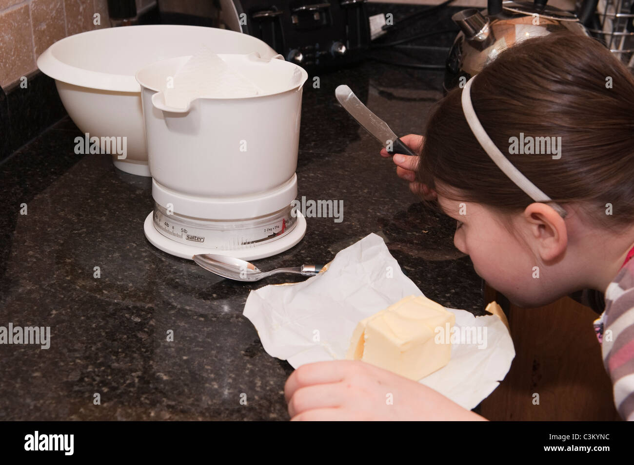 A young girl baking, checking closely the reading on the weighing scales. - Stock Image