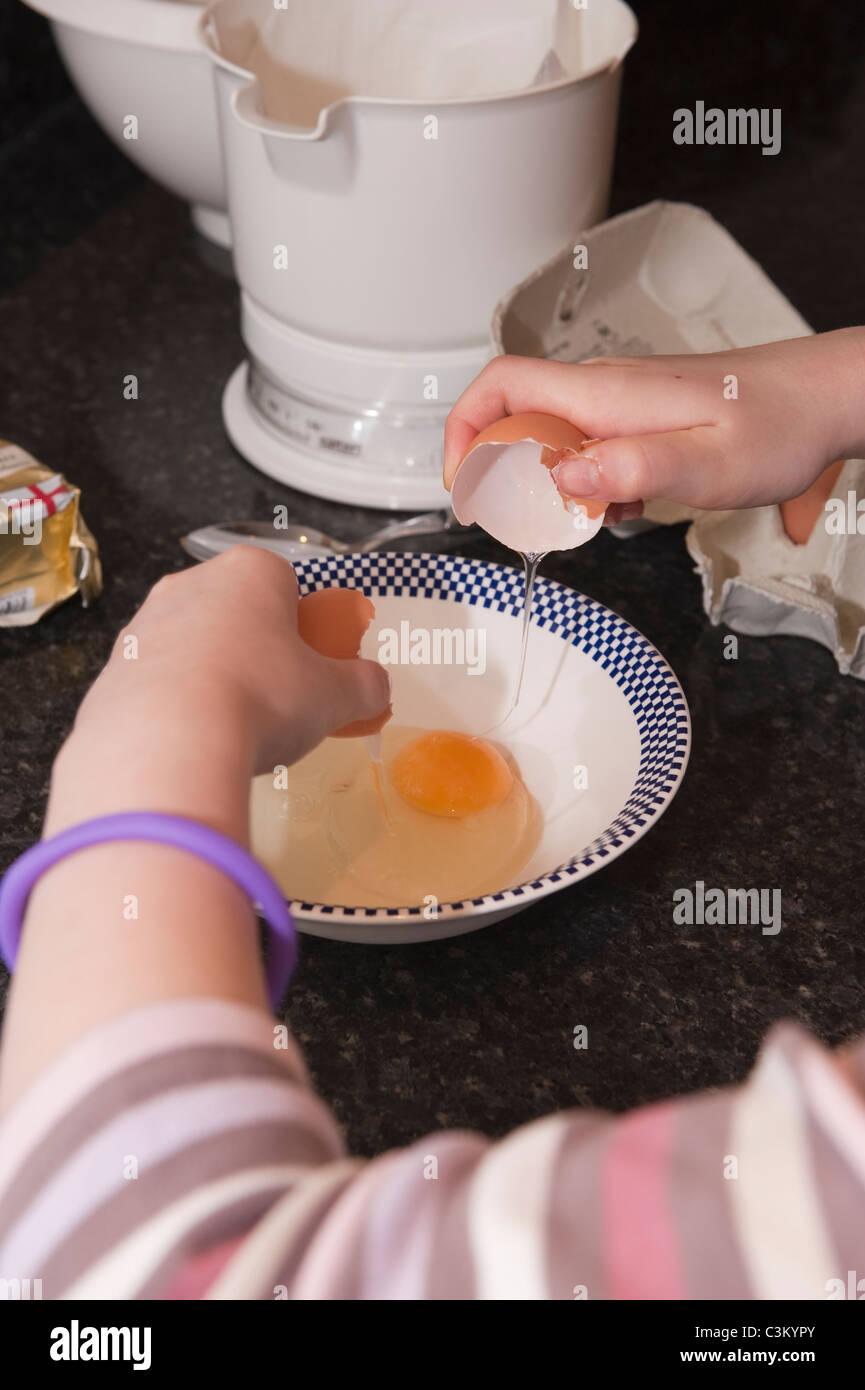 A young girl baking cracking an egg into a bowl. - Stock Image