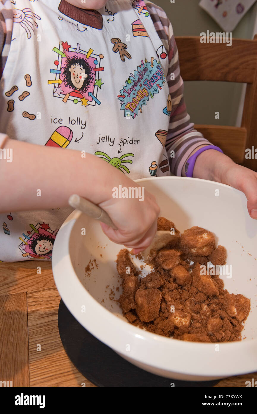 A young girl baking, stirring the ingredients in her bowl. - Stock Image