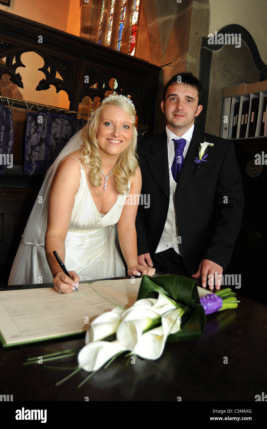 A couple sign the marriage registers during the ceremony at their wedding - Stock Image
