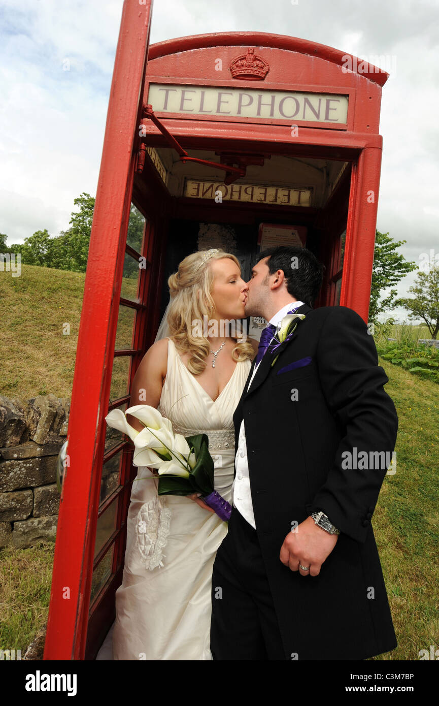 528f5de32a5 British traditional bride and groom kiss in a traditional red phone box on  their wedding day