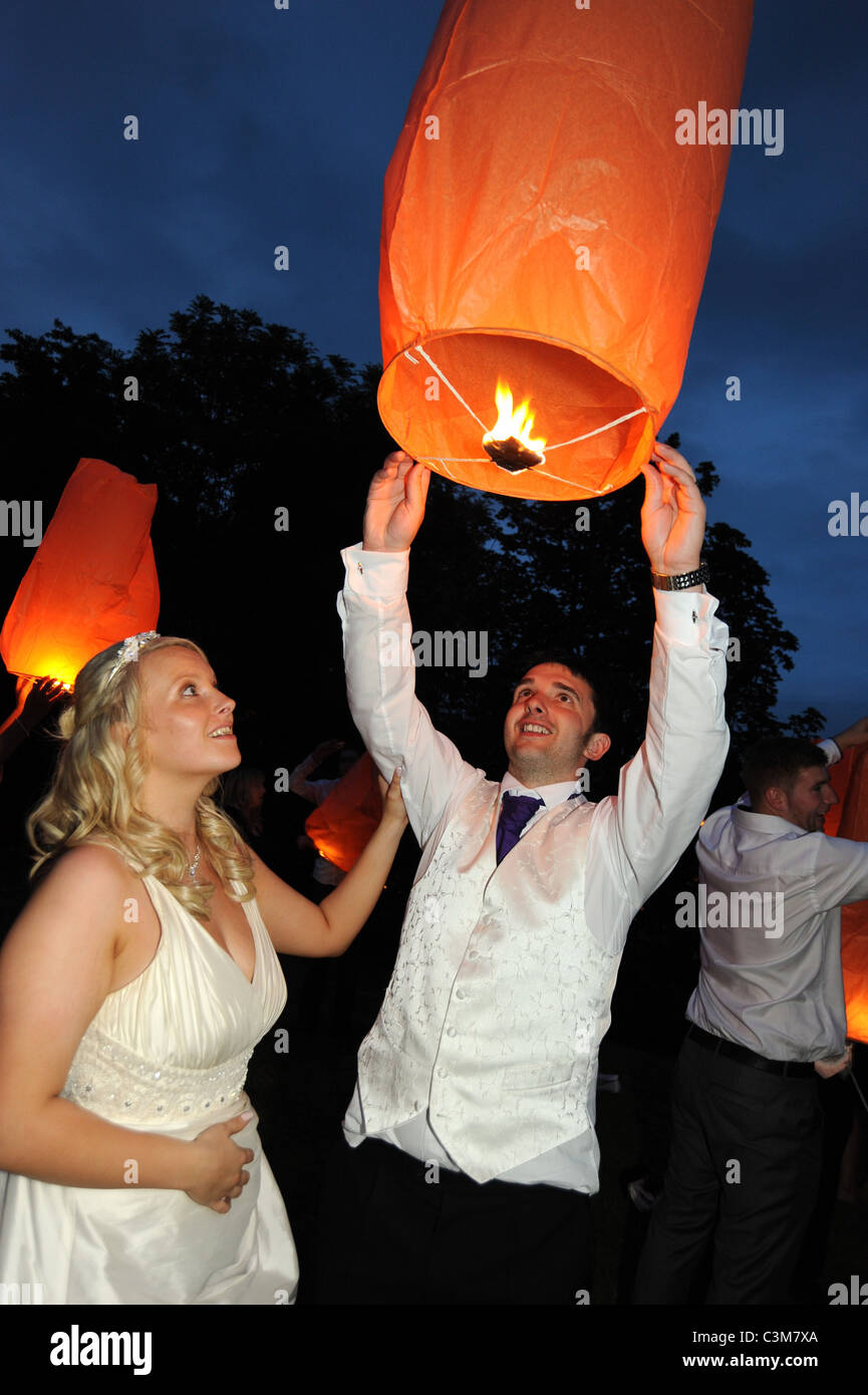 A newly married couple launch a Chinese lantern at the wedding party reception - Stock Image
