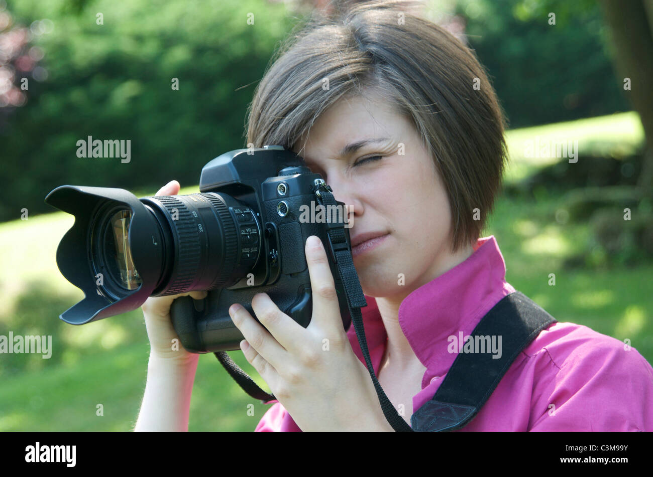 Young woman / teen taking photo with a digital camera (dslr) - Stock Image