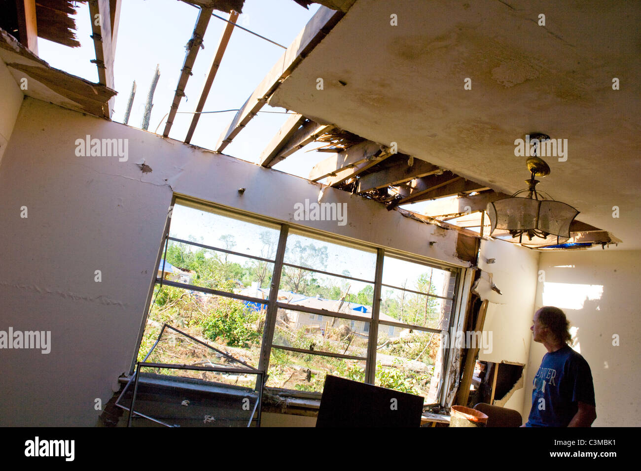 Man looks through window of his damaged home, after tornado struck his neighborhood near Tuscaloosa, Alabama, USA - Stock Image