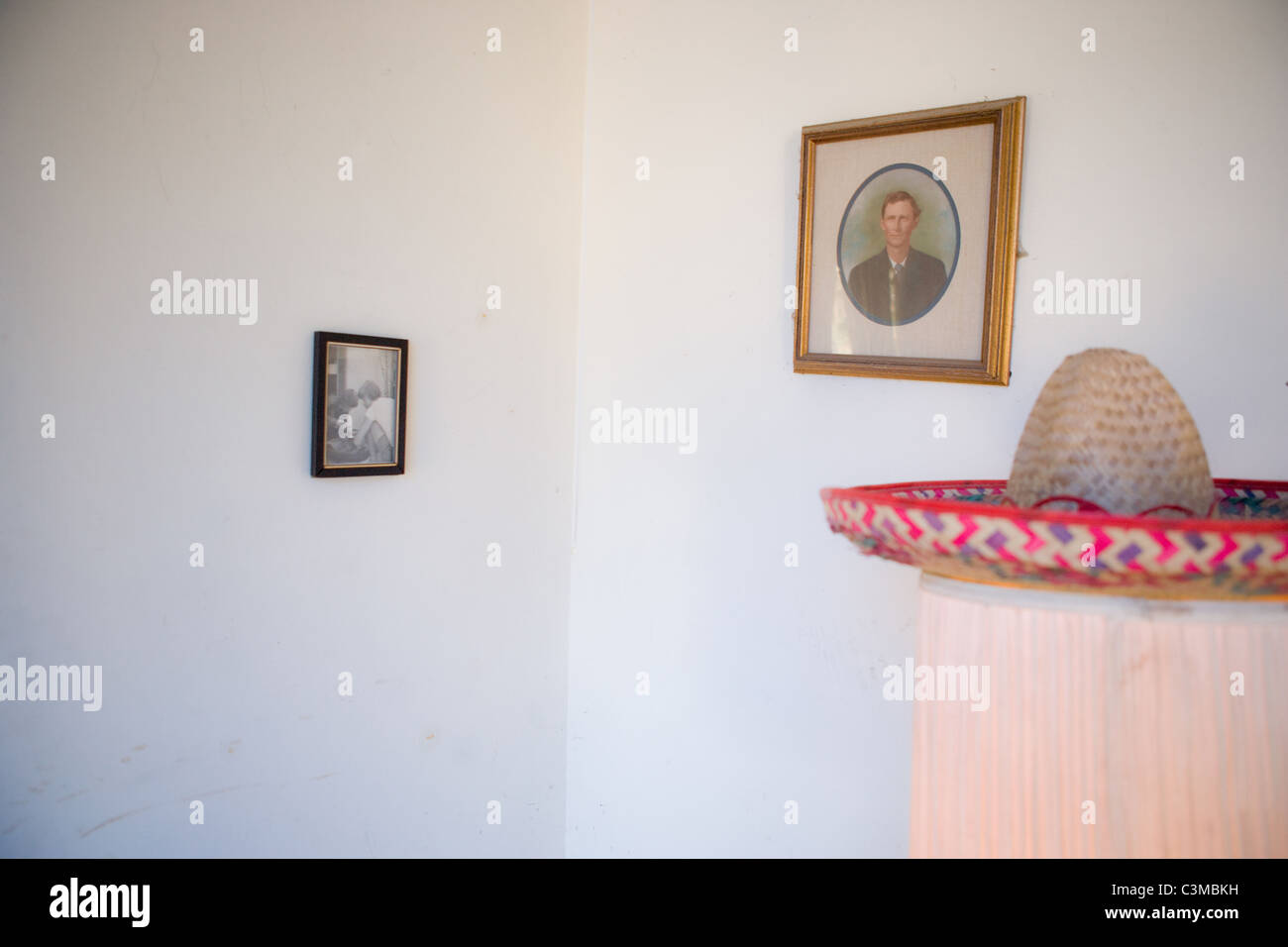Living room with two old family portraits on the walls, and a sombrero. - Stock Image