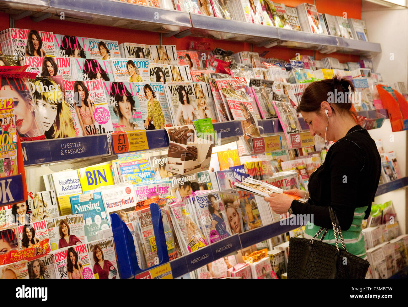 A woman buying magazines in WH Smith store, Cambridge UK - Stock Image