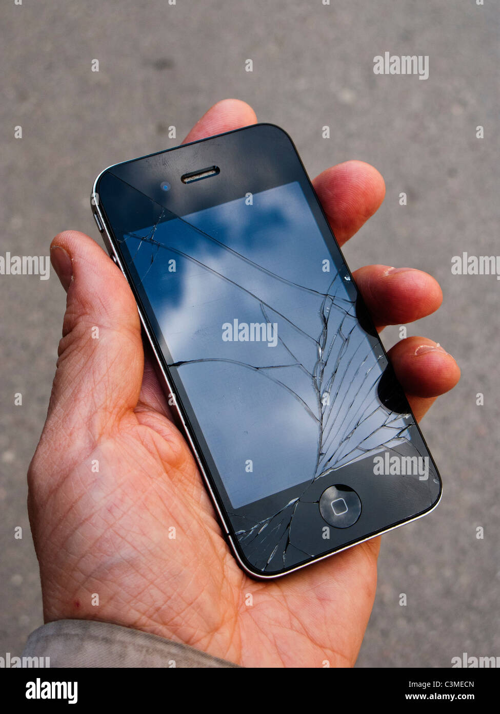 Cracked glass of an iPhone 4 in the palm of a hand - Stock Image
