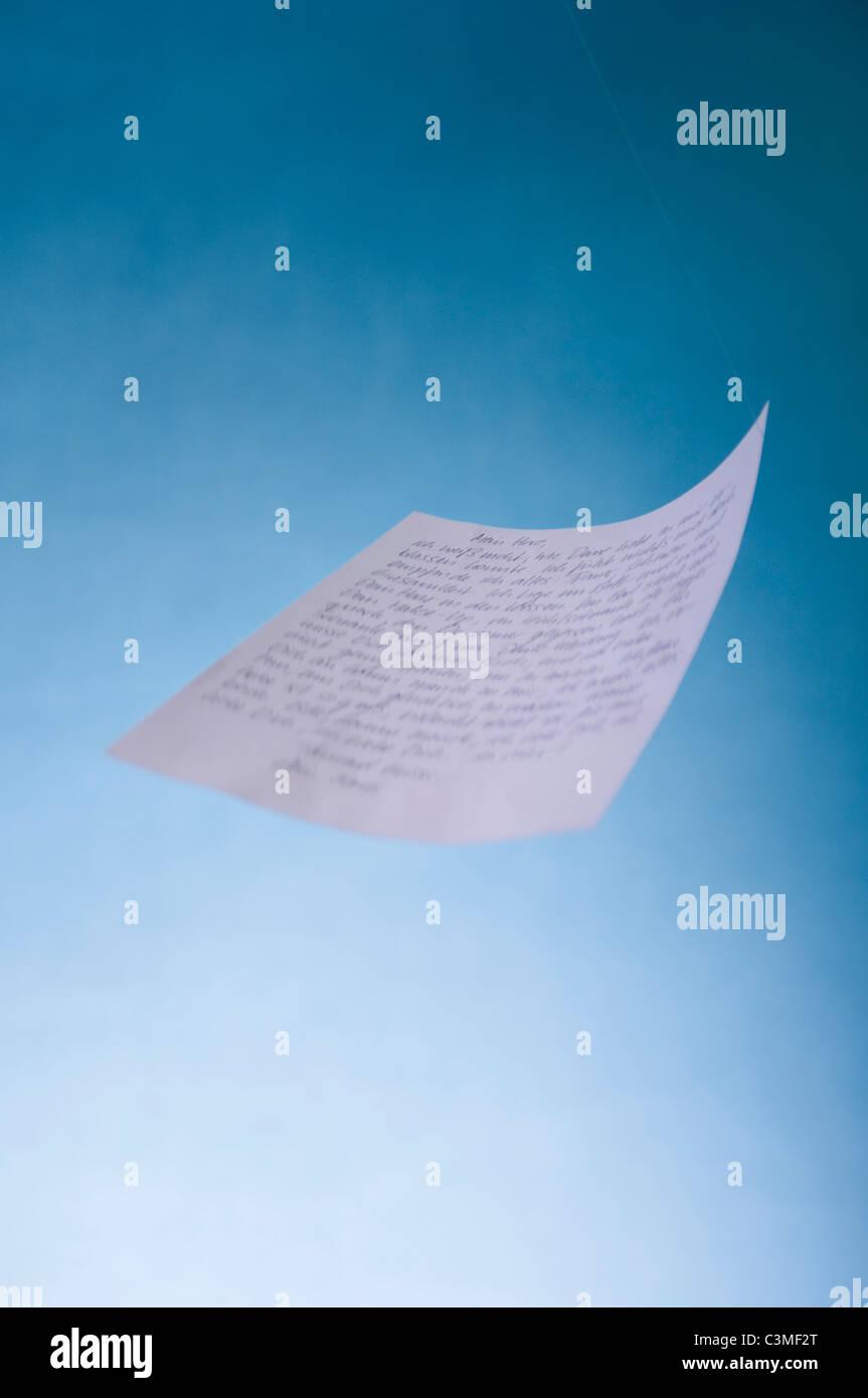 Love letter falling against blue background - Stock Image