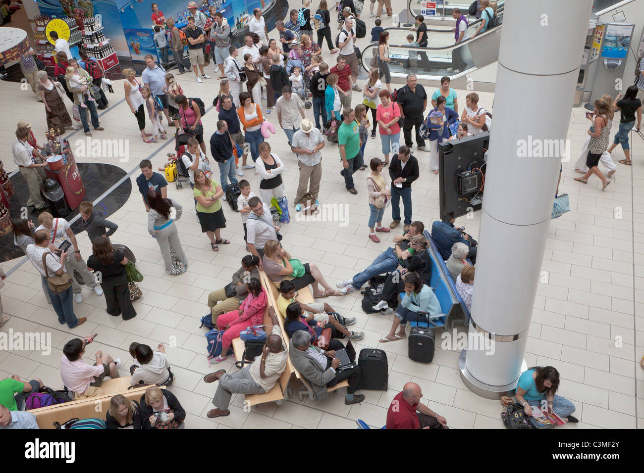 Passengers waiting for flight information at the departure lounge of the south terminal at Gatwick Airport, England - Stock Image
