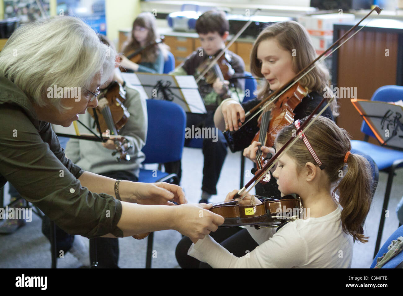 Young violinists playing their violins in  a youth music group / orchestra / band, with teacher helping a child - Stock Image