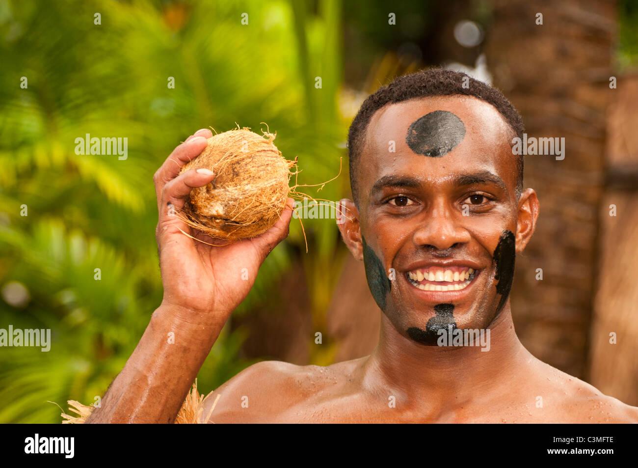 Tradtional Fijian warrior performs cermony with mature coconuts, Castaways Resort, Qalito Island, Mamanucas, Fiji - Stock Image