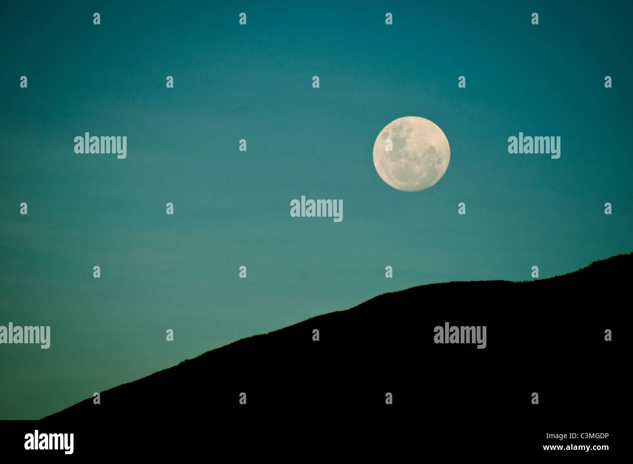 Full moon rising over the Mountains of the Yawasa Islands, Fiji - Stock Image