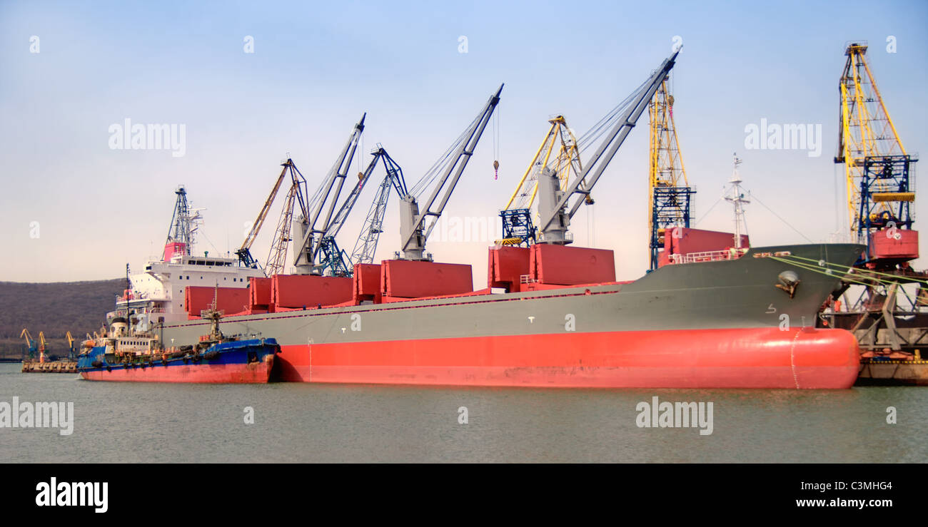 A cargo ship is being loaded with coal - Stock Image