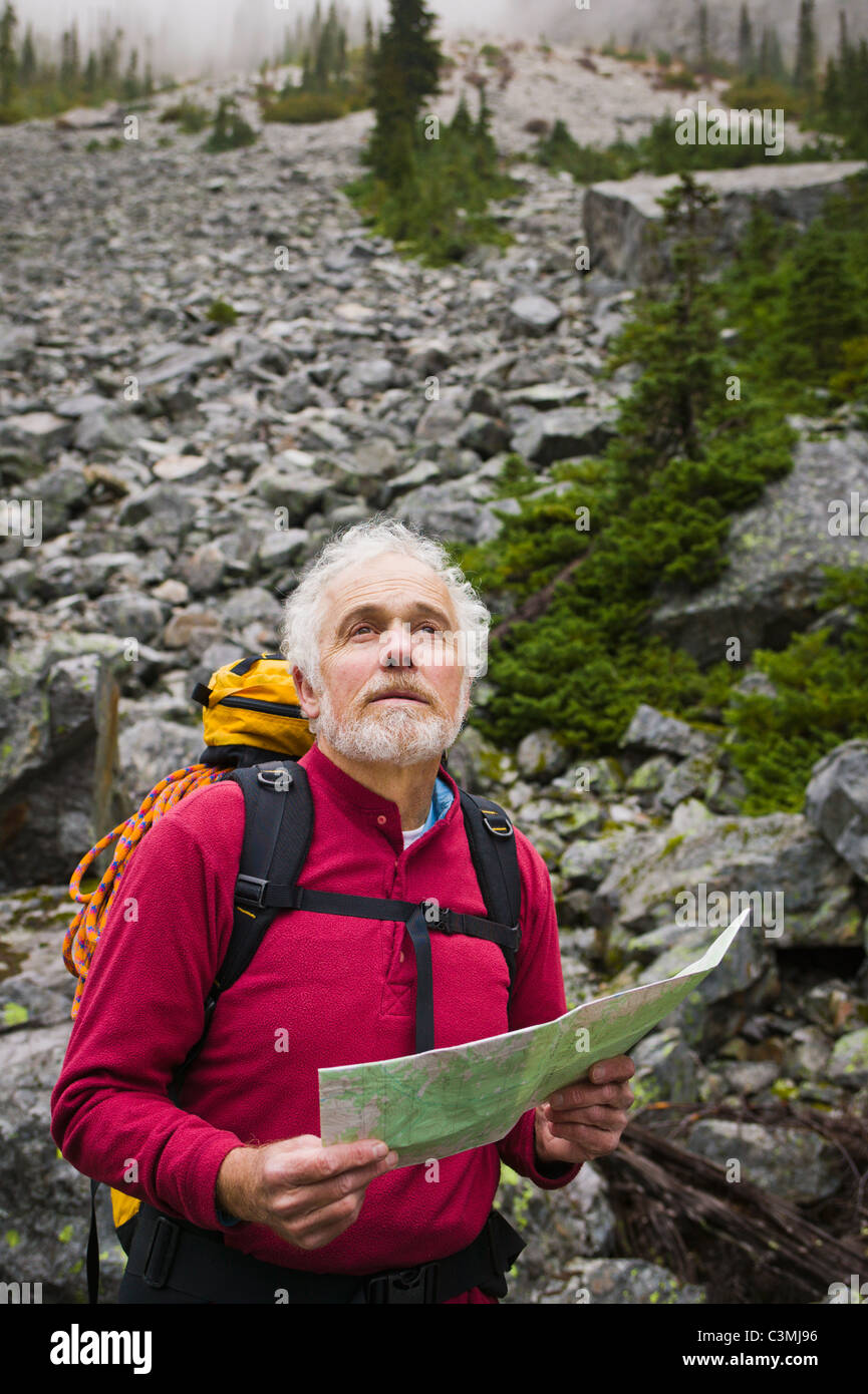A mature man out in the wilderness usinga map to find his way. Washington Cascades, USA. - Stock Image