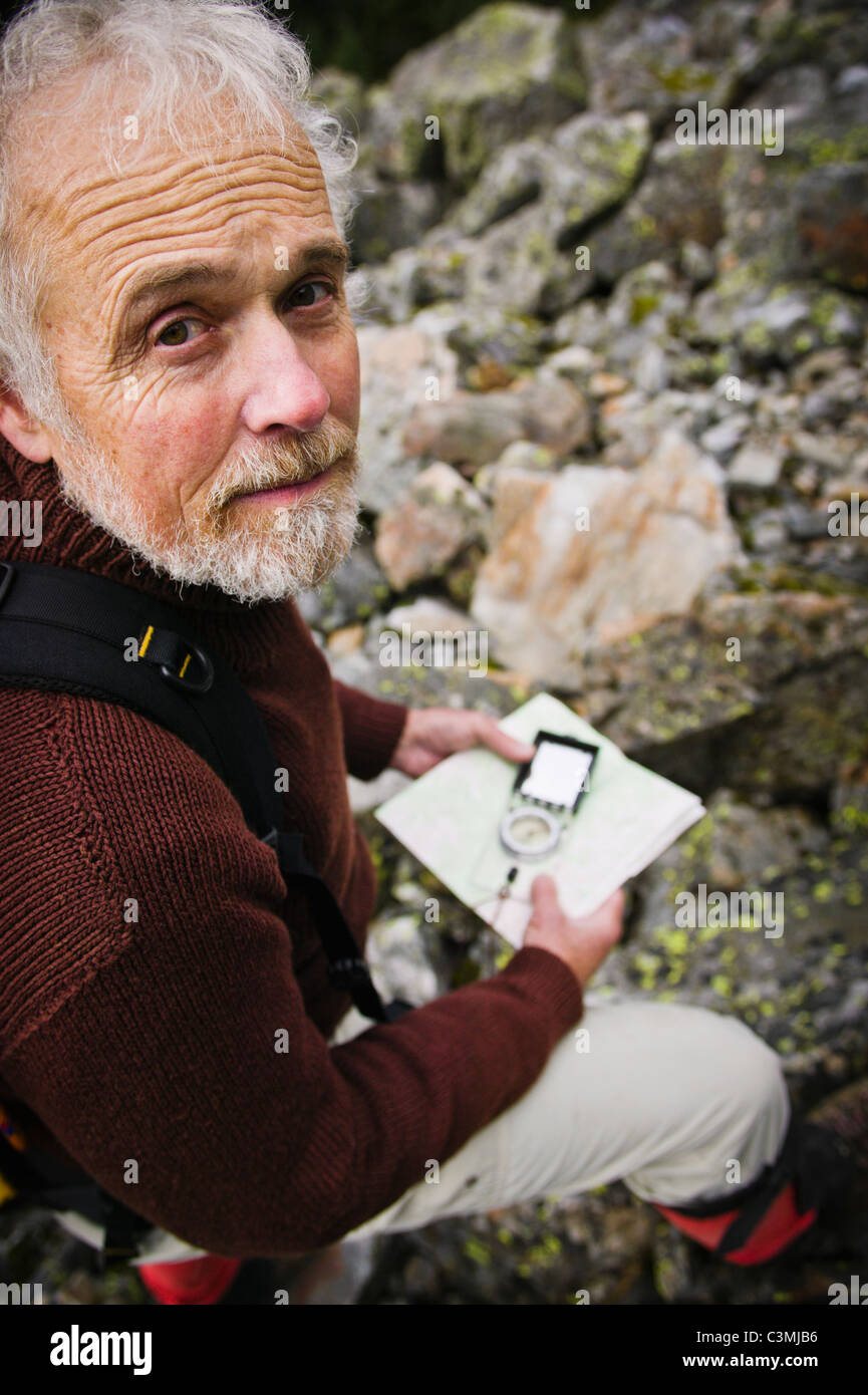A portrait of a man using a map and compass. - Stock Image