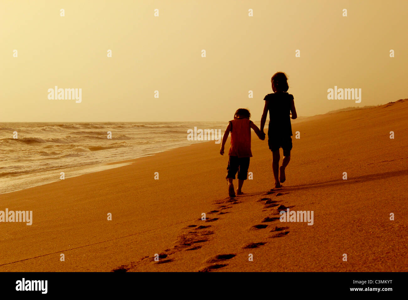Girl and boy walking on a beach with foot prints left behind - Stock Image