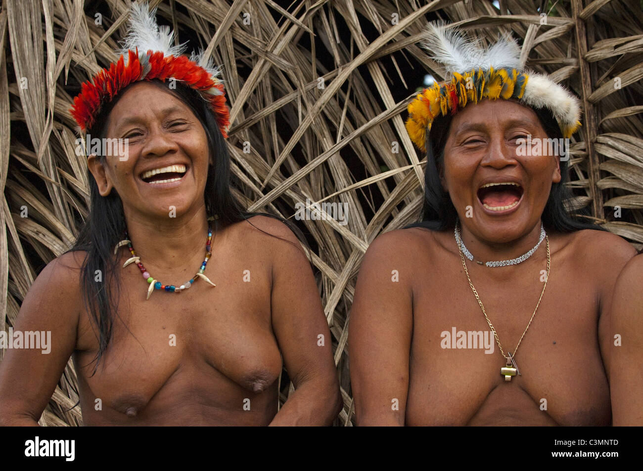Huaorani Indians: Laughing women (Awame Gomoke and Dete Iteka). both wearing crowns topped with Harpy Eagle feathers - Stock Image