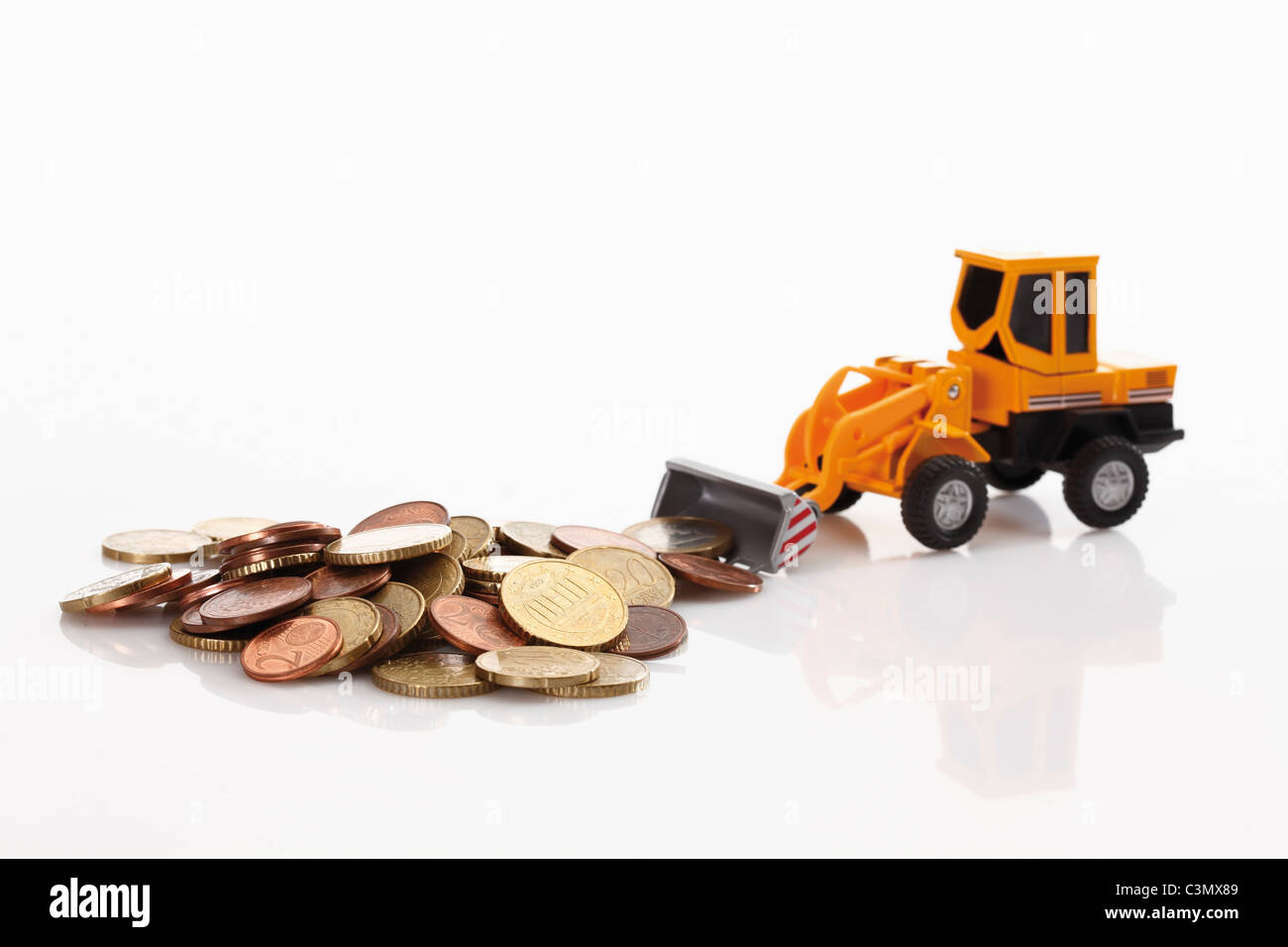 Toy bulldozer with euro coins on white background - Stock Image
