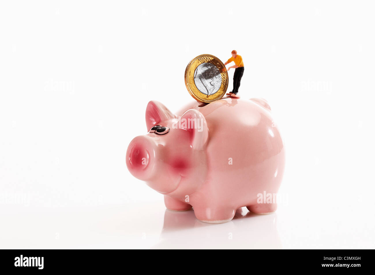 Figurine with 1 euro coin on piggy bank - Stock Image