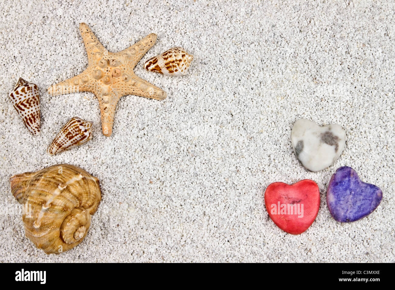 a seastar and several shells in white sand with three hearts - Stock Image