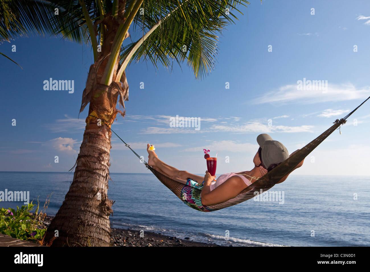 Indonesia, Island Bali, near Tejakula village, Gaia Oasis Resort. Women, tourist, in hammock drinking fruit cocktail. - Stock Image