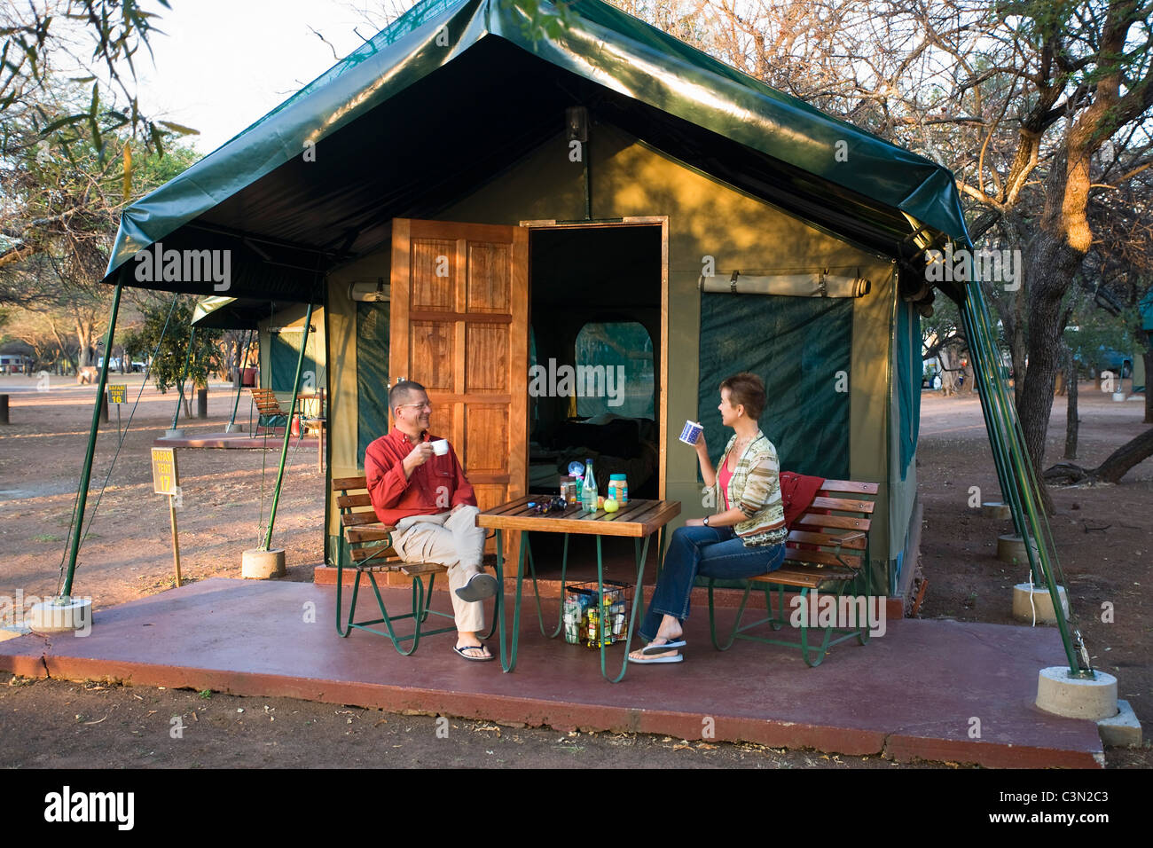 South Africa, Pilanesberg National Park Couple, man and woman, having breakfast in front of safari tent at campsite - Stock Image