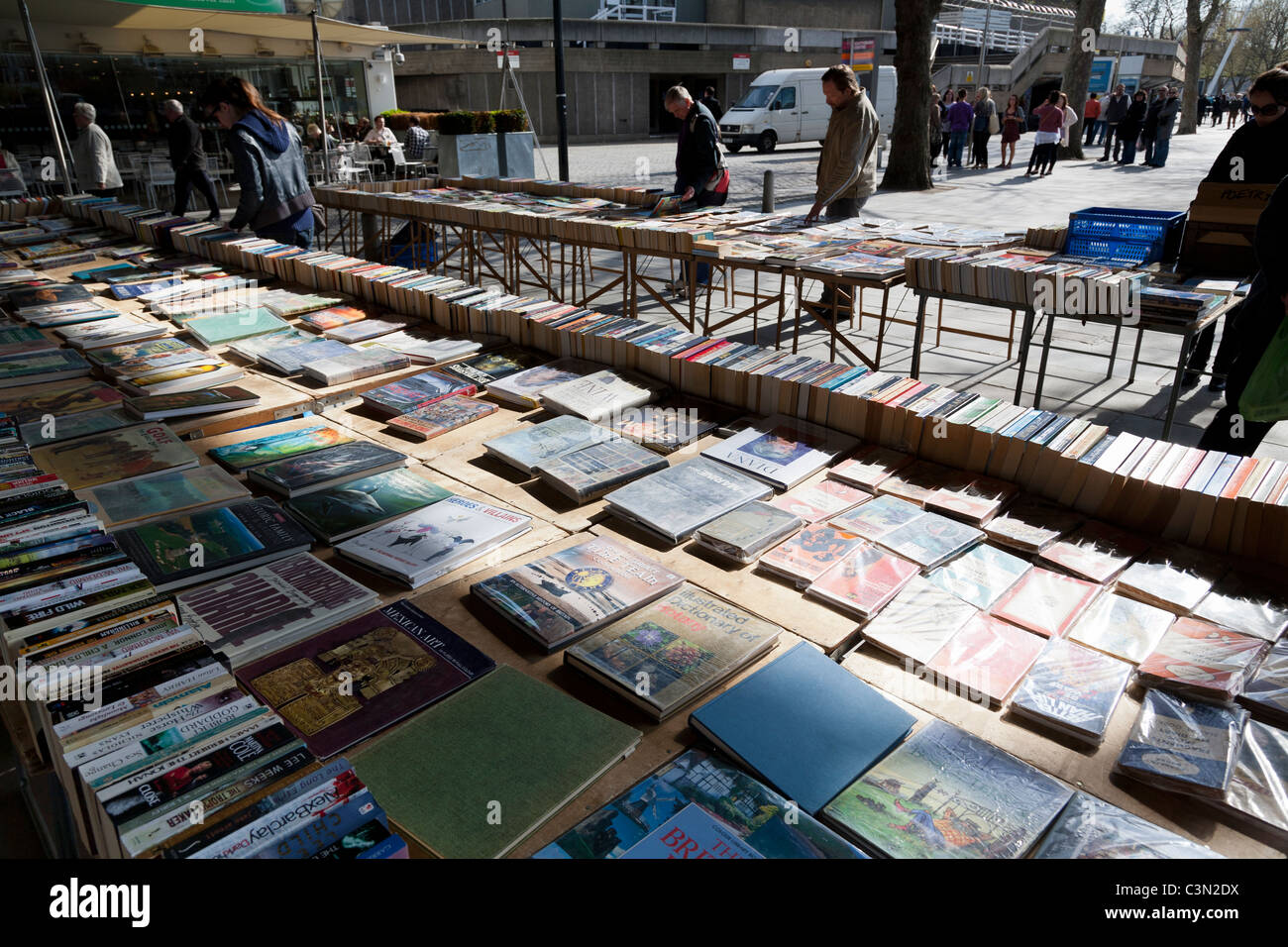 Shoppers peruse a display of books at an open-air book shop on the South bank, London. - Stock Image