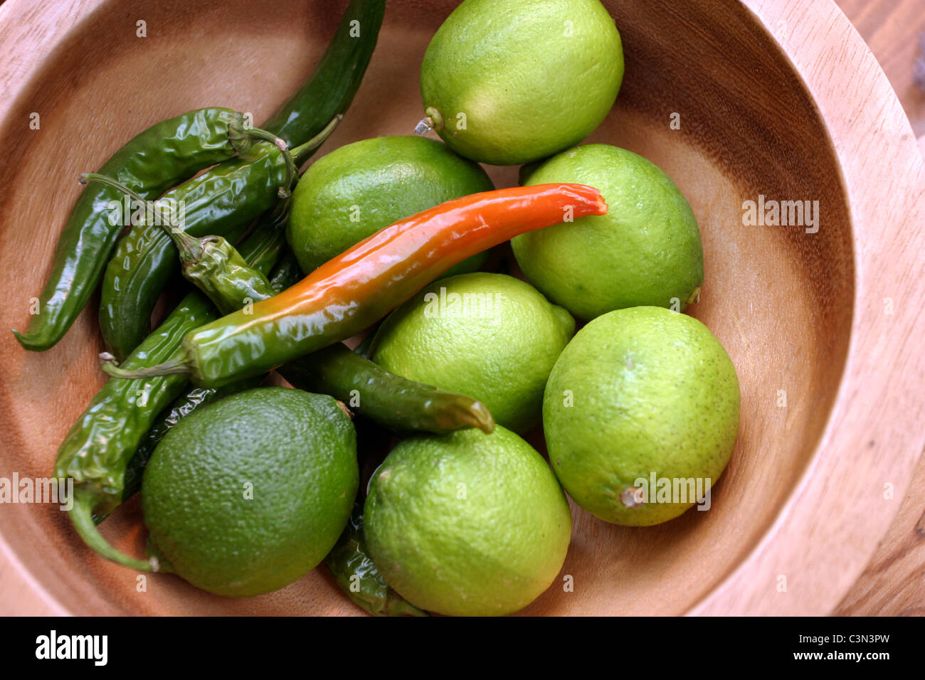Limes and Green Chillies in a Bowl - Stock Image