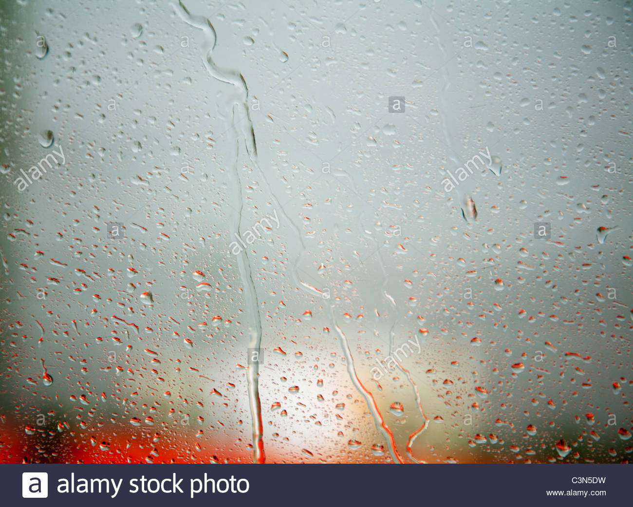 Rain droplets on window, red bus behind - Stock Image