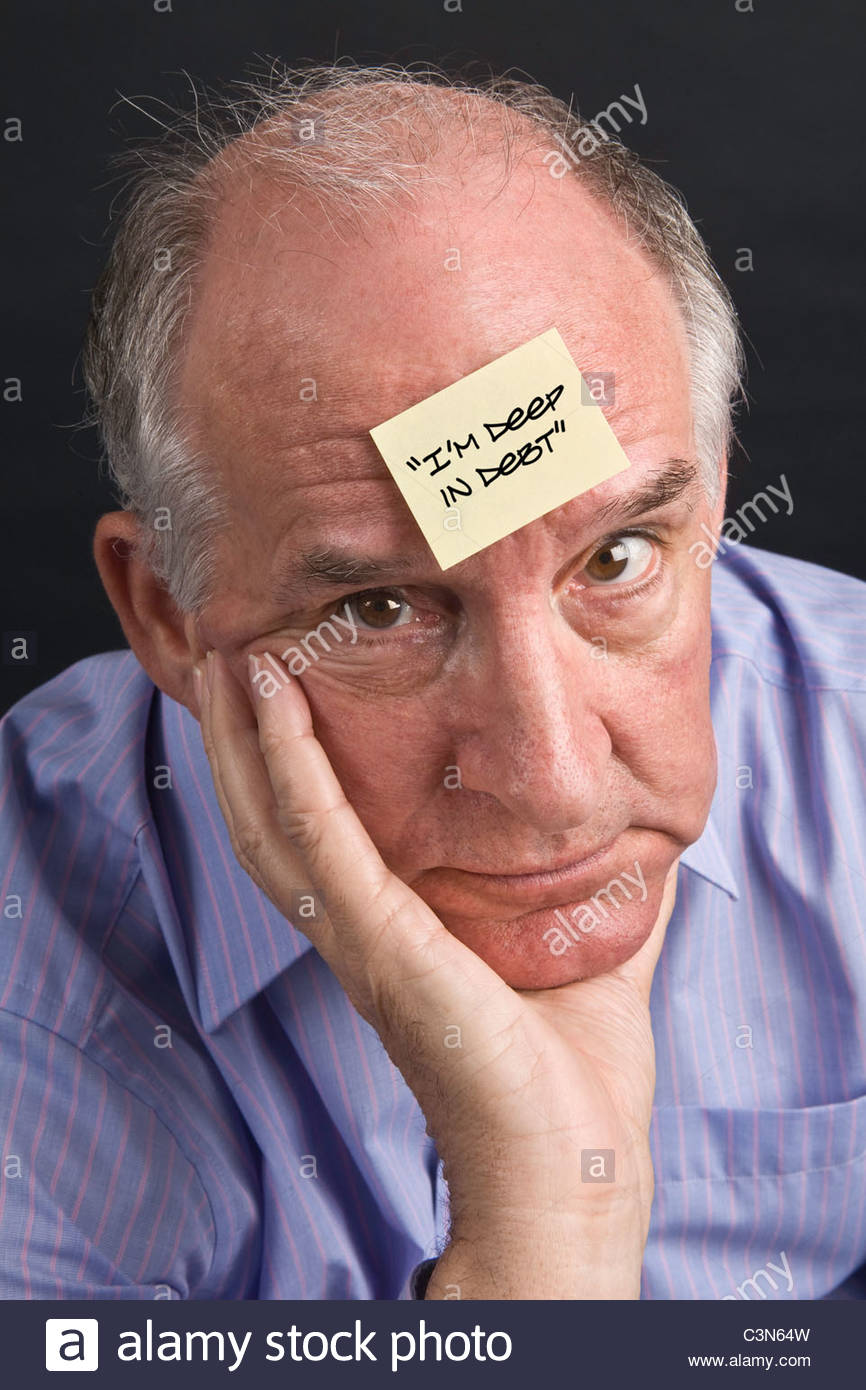 Mature male looking at the camera but very worried that he is in deep debt - Stock Image