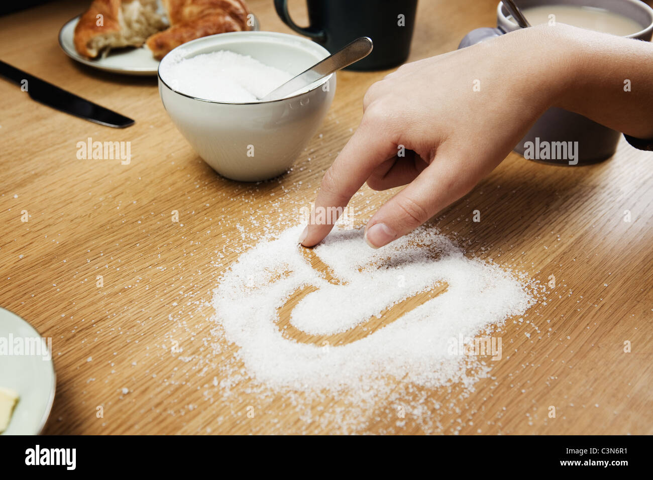 Girl drawing hart in sugar on table - Stock Image