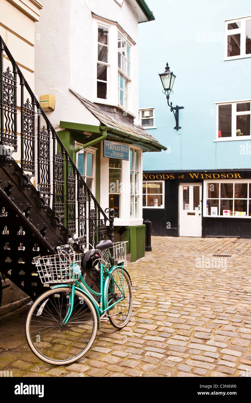 Green bicycle at bottom of  wrought iron staircase by Crooked House, Market Street a cobbled street in Windsor, - Stock Image